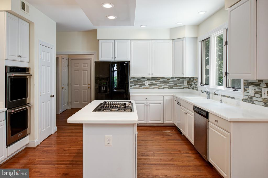 The kitchen features white cabinets, - 1144 ROUND PEBBLE LN, RESTON