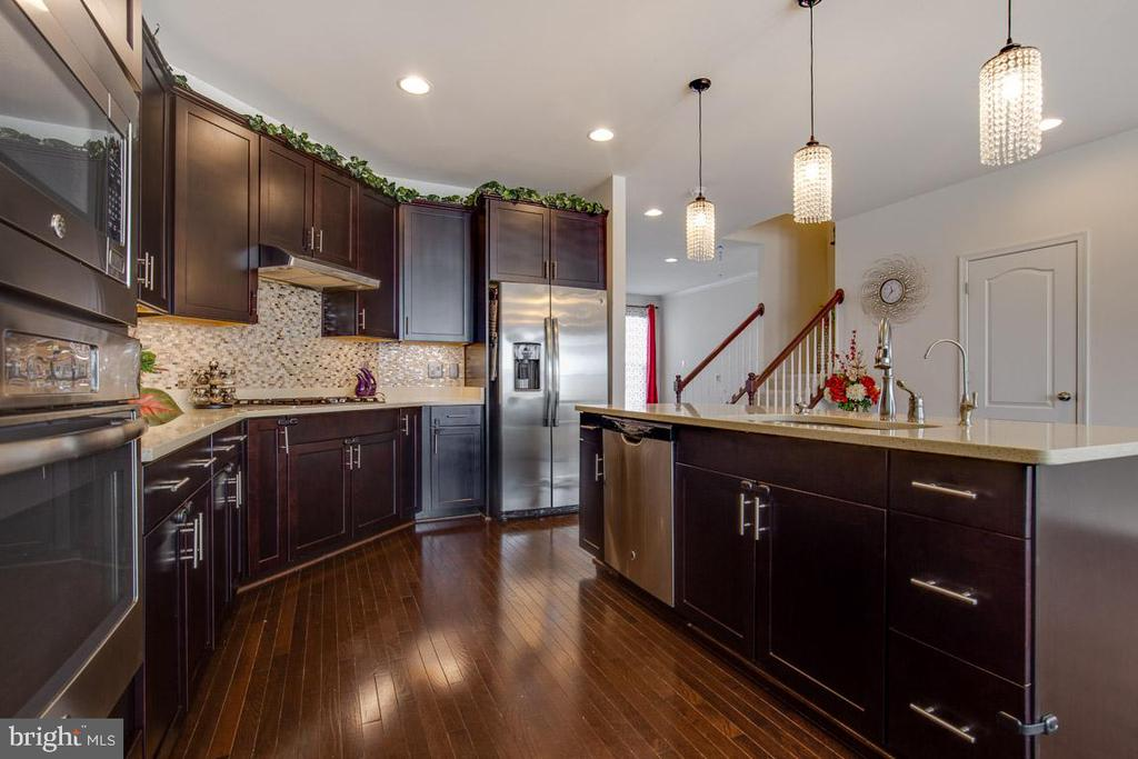 Kitchen with hardwood floors on main level. - 24684 CAPECASTLE TER, ALDIE