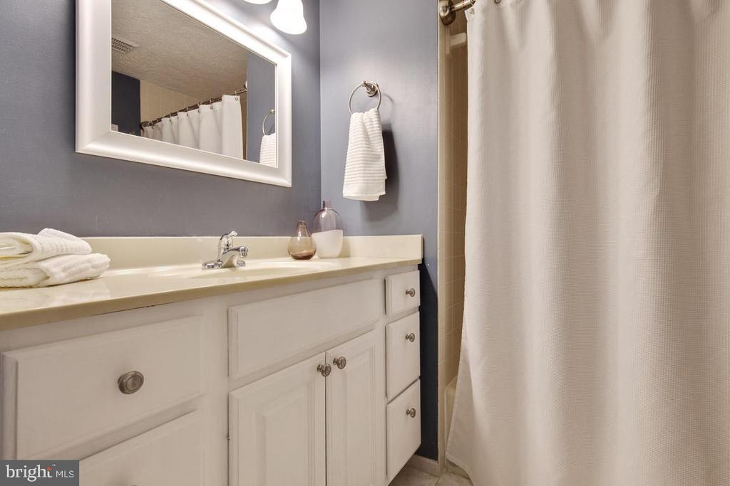 Hall bathroom with tub and large vanity - 8419 RAINBOW BRIDGE LN, SPRINGFIELD
