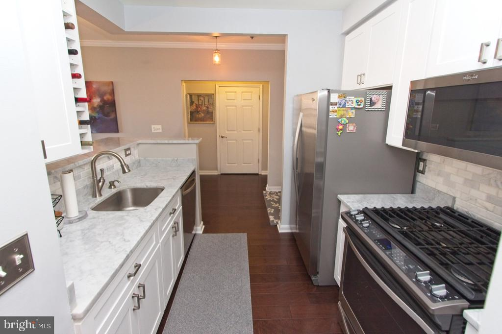 Stainless appliances include a 5-burner gas stove - 1855 STRATFORD PARK PL #309, RESTON