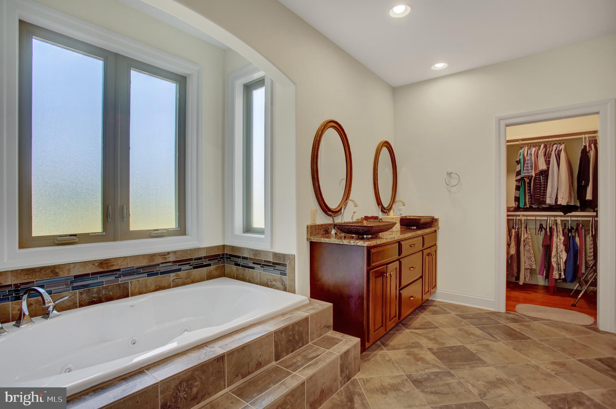 Ensuite with tub, double vanity, & walk in closet.
