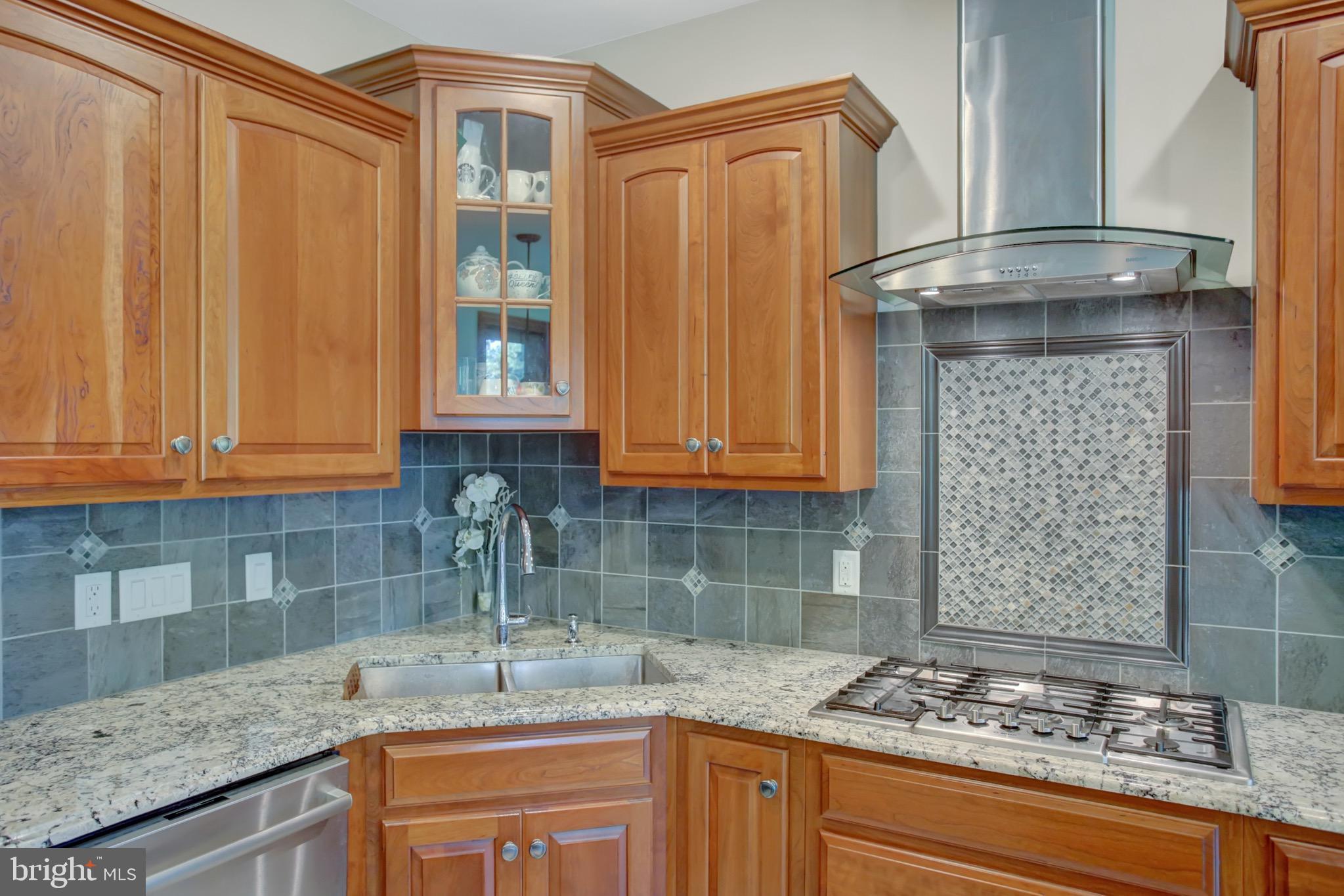 Tile backsplash, gas cooktop, stand alone vent.