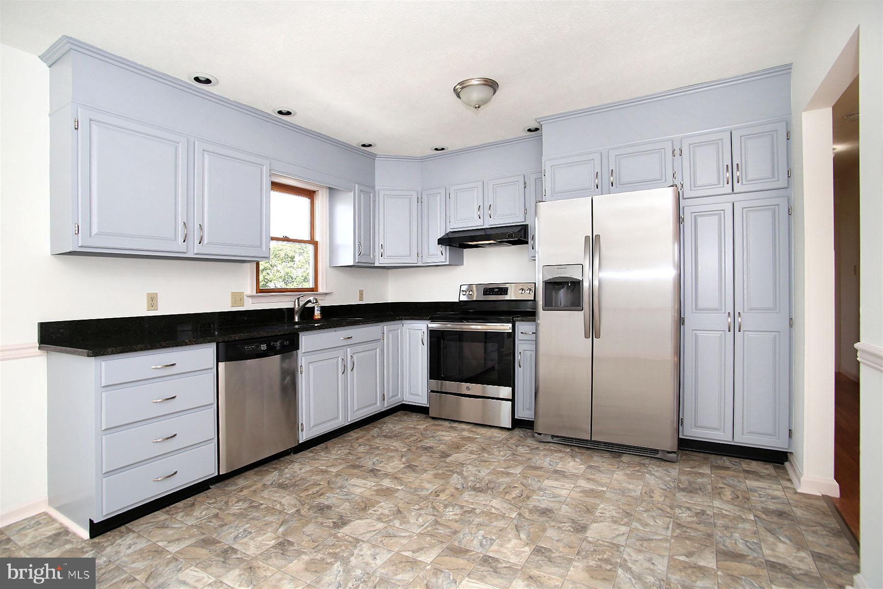 Kitchen with SS appliances & granite counter tops.