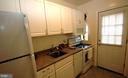 Galley kitchen with white cabinets. - 316 ASHBY ST #D, ALEXANDRIA