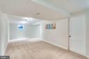 Basement rec room w/ entrance to storage/workshop - 6411 WYNGATE DR, SPRINGFIELD