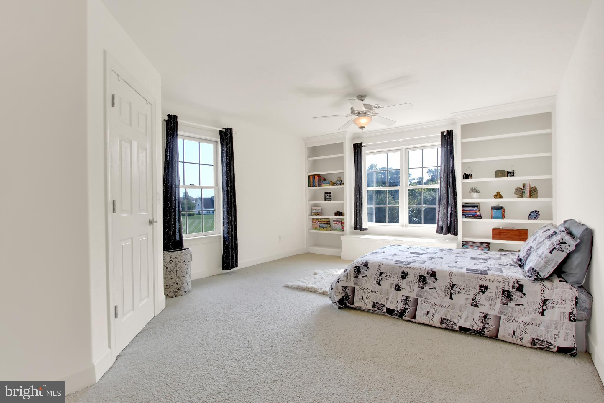Bedroom with built-in shelving and walk-in closet