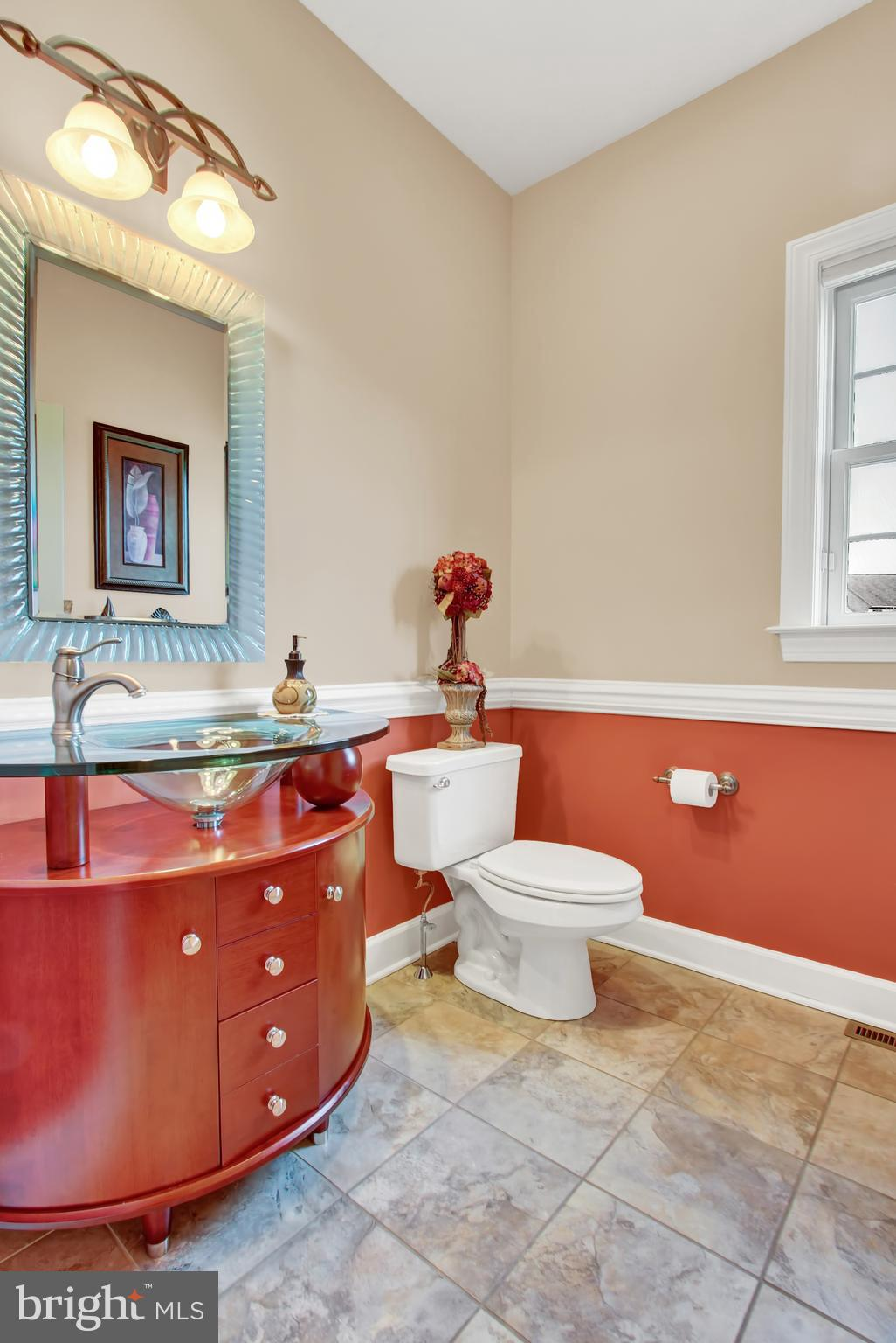 Half bath with glass bowl sink and tile flooring