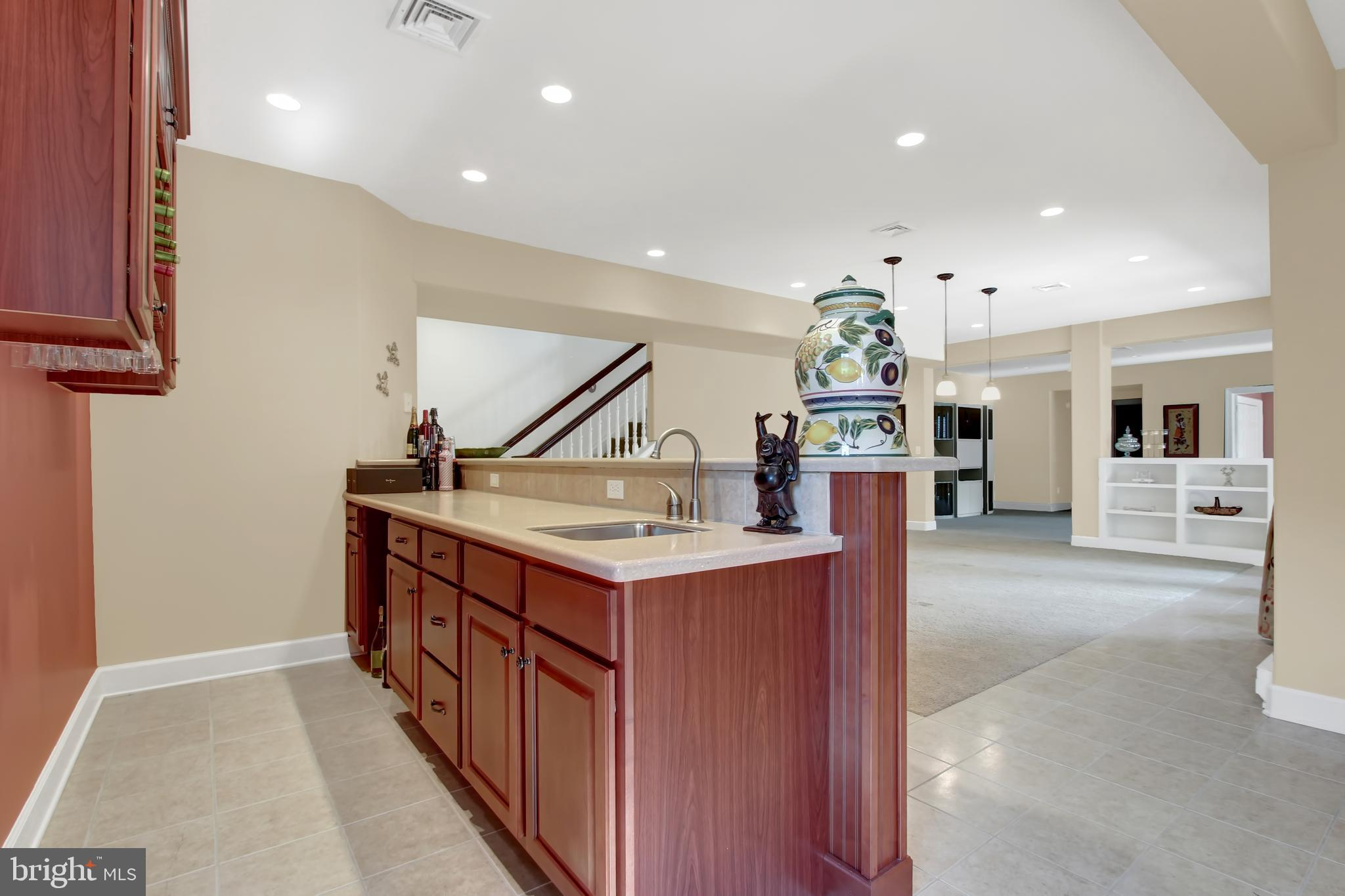 Open, finished basement with built-in wooden bar