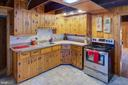Kitchen with stainless stove and refrigerator - 16657 TREE CROPS LN, ROUND HILL