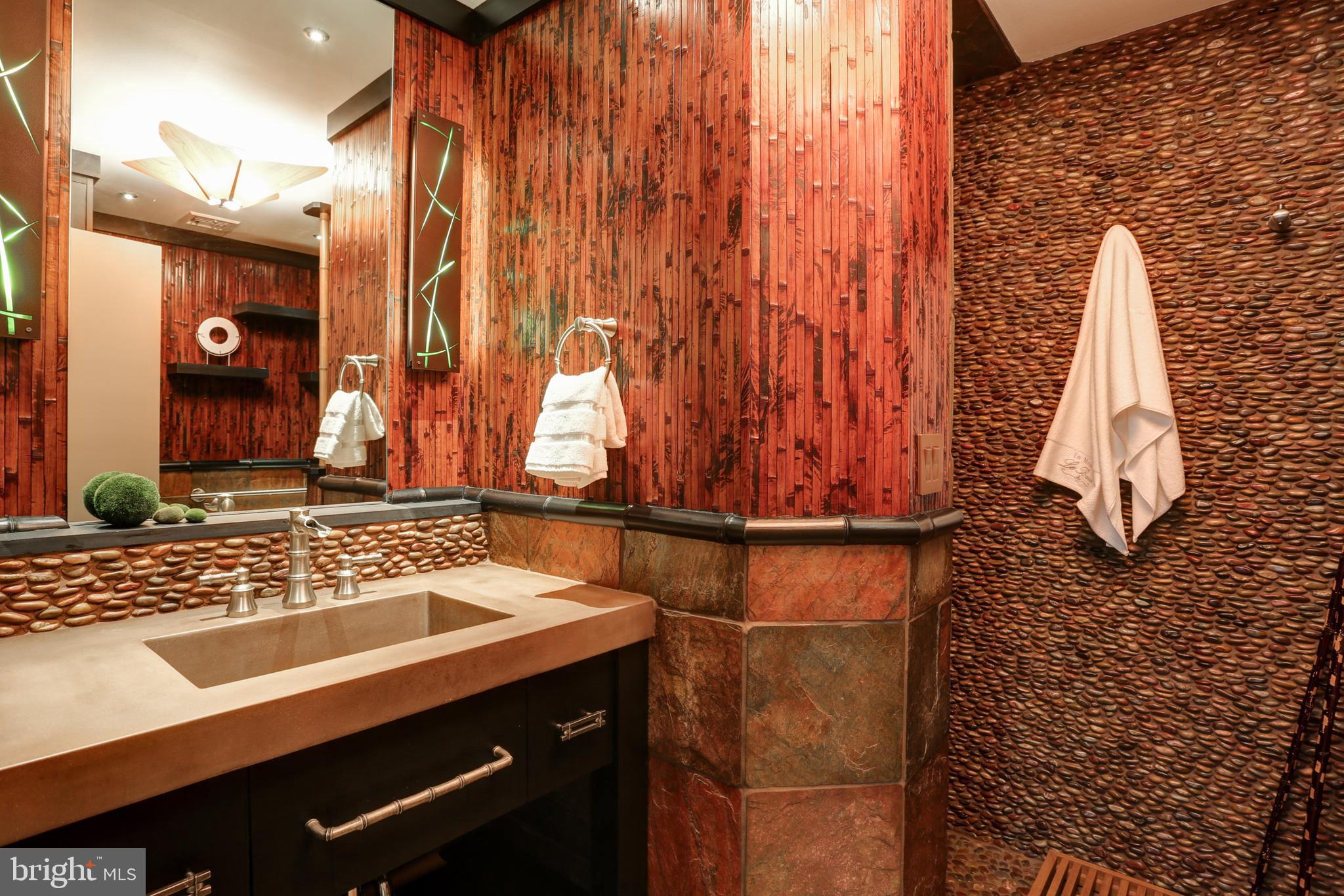 Convenient main floor bamboo and river rock bath.
