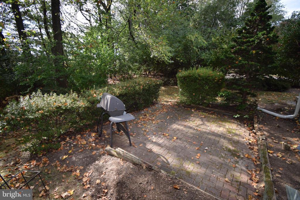 Brick patio in backyard surrounded by trees - 11690 STOCKBRIDGE LN, RESTON
