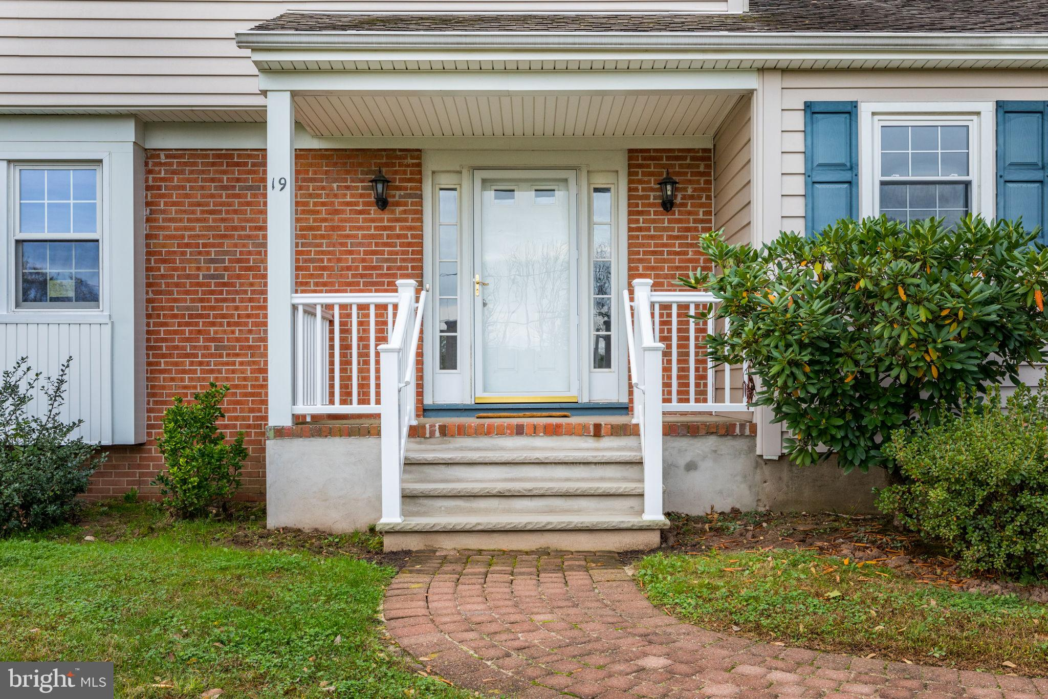 covered front porch with brick walkway