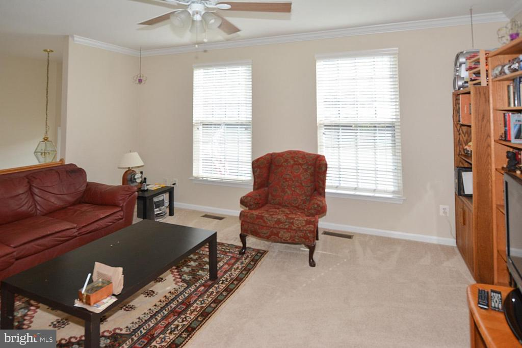 Living room with ceiling fam and newer carpet - 9315 PAUL DR, MANASSAS PARK