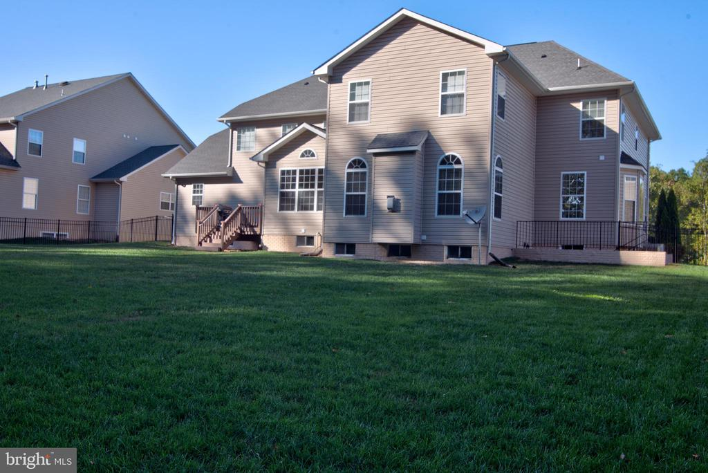 The rear deck and basement exit are featured here. - 38 PRESIDENTIAL LN, STAFFORD