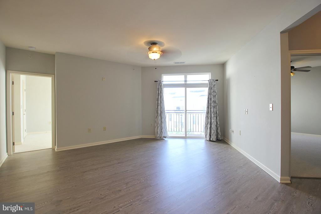 Open living room with balcony and hardwood floors! - 2665 PROSPERITY AVE #429, FAIRFAX