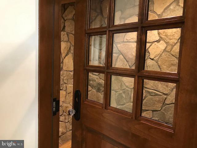 Custom alder door leads to wine room w/stone walls - 2222 KING ST, ALEXANDRIA