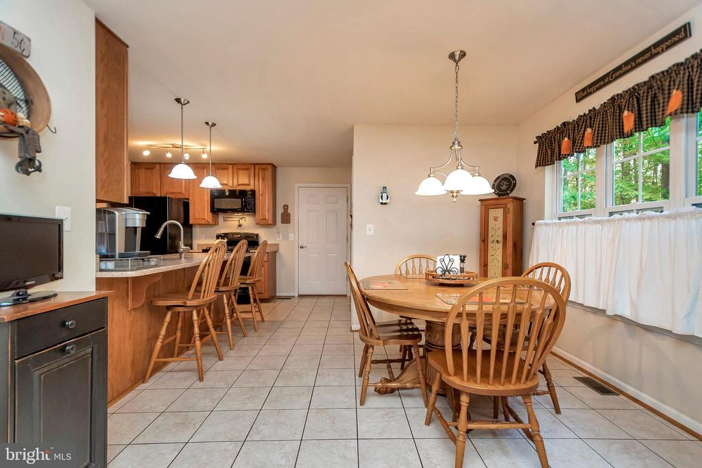 Kitchen offers ample table space and breakfast bar - 404 WILDERNESS DR, LOCUST GROVE