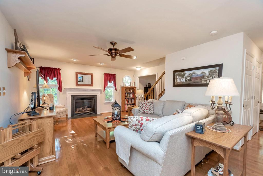 Family room boasts gleaming hardwoods - 404 WILDERNESS DR, LOCUST GROVE