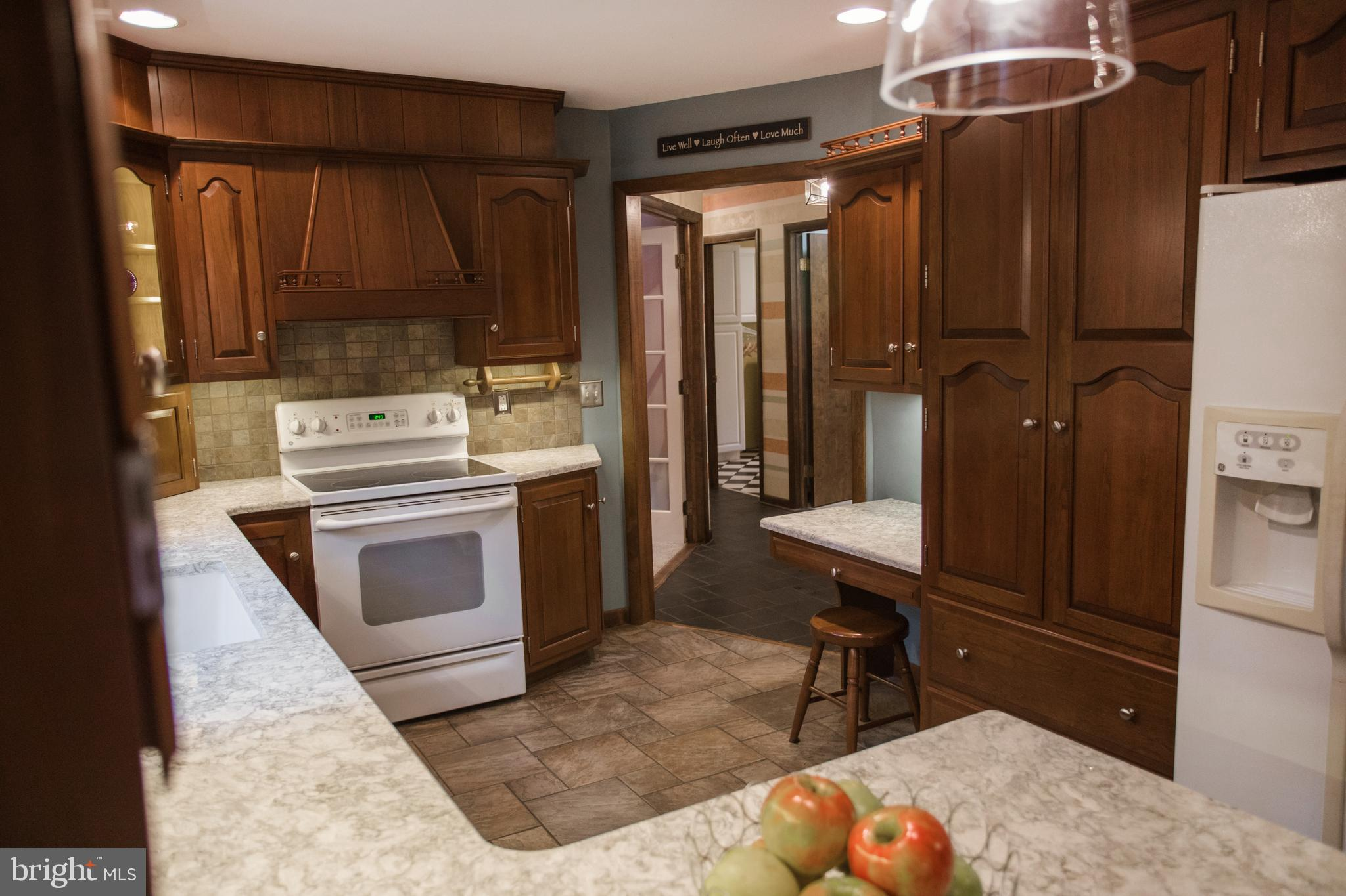 Kitchen features custom cabinetry, pantry