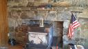 stone wall with woodstove - 260 WHITE HALL RD, WINCHESTER