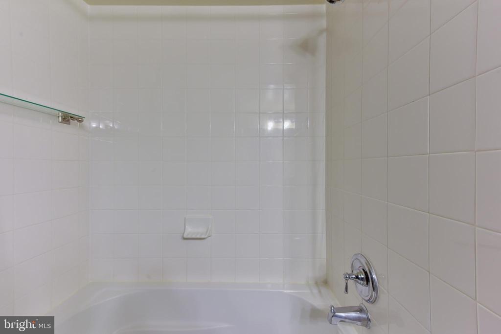 White shower tub in master bathroom. - 4165 S FOUR MILE RUN DR #204, ARLINGTON