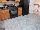 Beautiful newer vinyl tile flooring in kitchen - 9315 PAUL DR, MANASSAS PARK