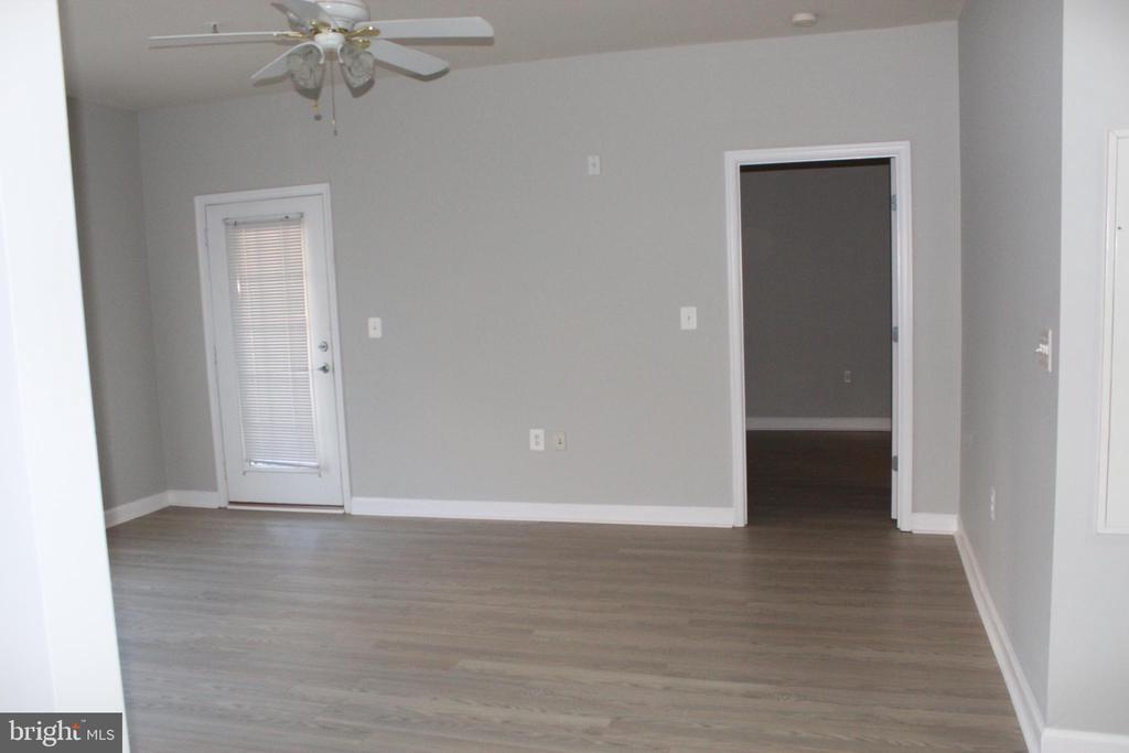 Living room - door to Patio and Bedroom - 42496 MAYFLOWER TER #101, BRAMBLETON