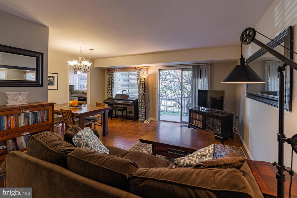 Living room with sliding glass door to balcony - 10655 WEYMOUTH ST #101, BETHESDA