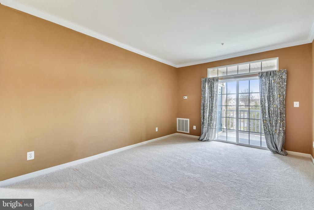 Living room w/crown moulding & door to balcony - 43415 MADISON RENEE TER #117, ASHBURN