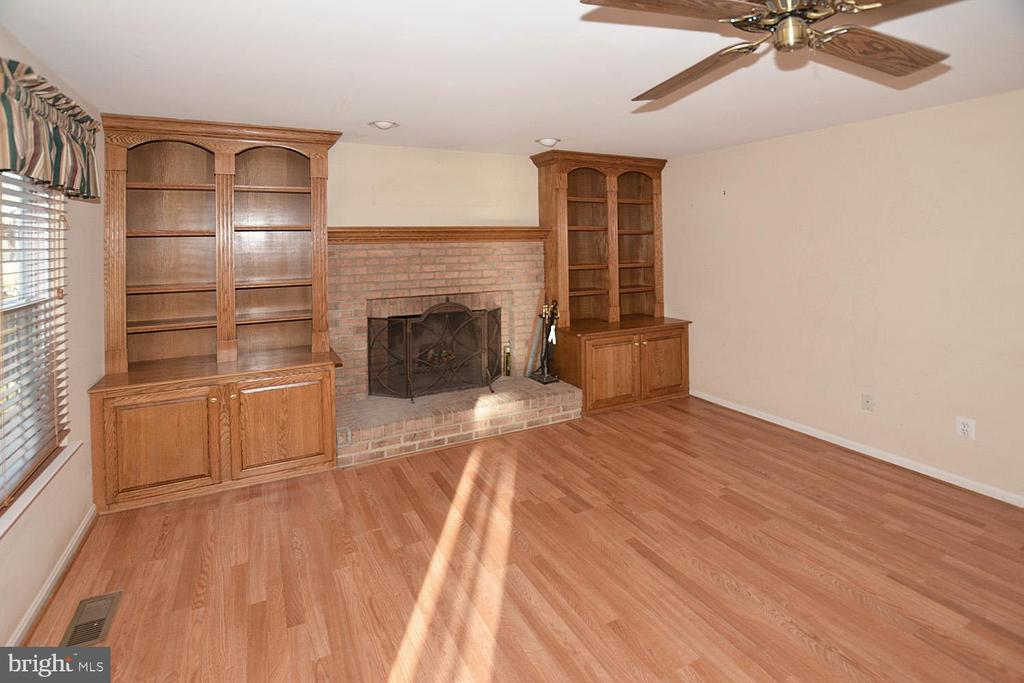 Family room with new wood laminate and fireplace. - 9337 S WHITT DR, MANASSAS PARK