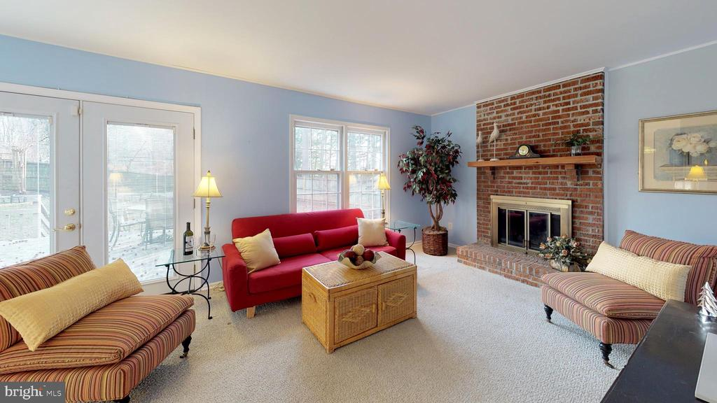 Window-filled family room with cozy fireplace - 6935 COLBURN DR, ANNANDALE
