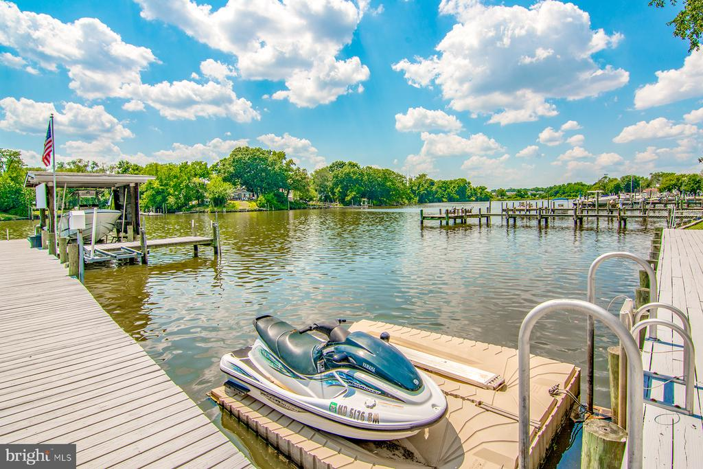AMAZING waterfront Retreat on Double Lot! Detached Garage, Sprawling Rancher, Boat Lift with Covered Boathouse!, 2 Jetski Lifts, Floating Jetski dock, Firepit, hardscape with built-in Grill, party patio, Brand new Roof & HVAC System -SO MUCH MORE!  Short boat ride to Key Bridge, Inner Harbor, Middle River, Tiki Lee's, and just down the river from the Hard Yacht!