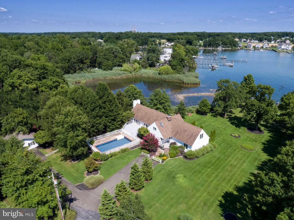 Tranquil waterfront paradise has it all! Private locale w/3400+ sqft contemporary home sited on a gorgeous 3.55 acre prof. landscaped lot, 100'+ private pier w/3 slips, lift, boat launch & waterside gazebo. Gourmet KIT w/SS appl., granite, brick FP, pantry & breakfast room. Sep. DR w/FP, huge great room w/FP & den. Main level master w/lg full bath, front & rear decks, detached garage, pool & more!