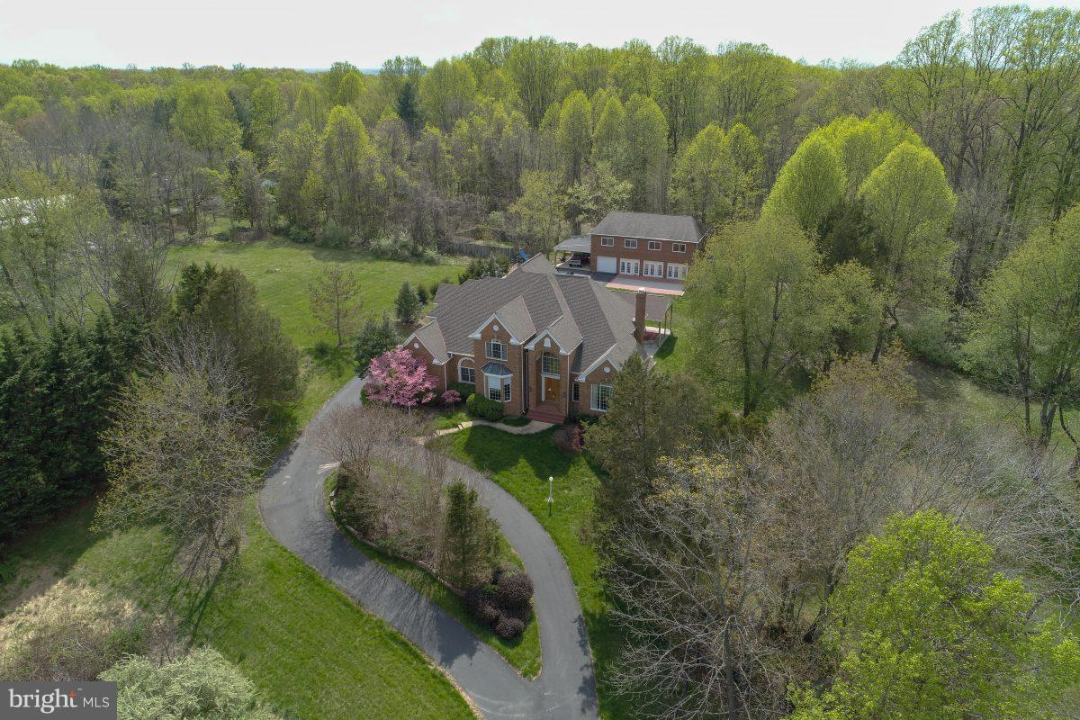 In the rolling equestrian countryside of Fairfax Station, Virginia; this Colonial majestic estate (with 7562 finished SF, 340 SF unfinished, and 660 SF 3 car garage, along with a 3200 SF Finished carriage house/pool house, 3 patios consisting of more than 2850 square feet, and a 1092 square feet of gazebo roof) sits high atop 5.03 acre, Minutes to Washington DC and Commuter options are close.