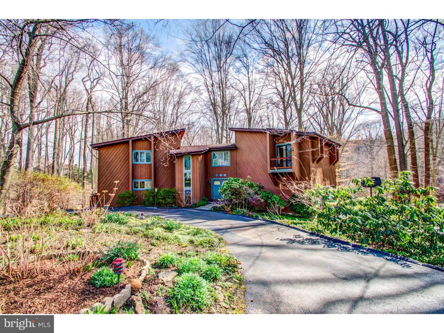 Welcome to this fabulous contemporary home situated in a private woodland retreat, yet only 5 minutes from the center of Hockessin. Enjoy the beautiful woodland views as you enter the circular driveway on this 1.5 acre property.  The main level opens to a sunken living room with light from the sliding doors streaming into the angles of the rooms and bamboo wood floors. A cozy wood-burning stove provides an additional heat source.  Step up to the dining area with wet bar and into the eat-in kitchen with custom wood cabinets, granite counters, eat-in island and double ovens.  Custom cabinetry in the breakfast area provides plentiful storage for glassware and linens. From there you have easy access to the main floor laundry room/pantry, as well as the powder room.  All rooms on the main level are surrounded by glass sliding doors to the 75' deck where you can entertain all your friends! The lower level of the home is finished with a large family room, powder room and a wet bar, with recently updated granite and new sink.  There is ample unfinished dry space for additional crafting or workshop. Pella sliding doors take you the brick patio with fire pit, where you can roast marshmallows or relax and watch the birds.  The oversized two-car garage has significant storage with built in cupboards and an extra high ceiling for bike storage or multi-layer cars. The upper level holds 4 generous bedrooms, each with a private balcony for reading, sunning or simply watching the wildlife. The freshly painted master is large & bright with a side room that can be used as a sitting room, office or closet/dressing room.  A walk-in closet and large master bath with Jacuzzi tub complete the room. The hall bath has a recently renovated walk-in shower and upgraded Carrara marble vanity top.  Take note of the multi-floor copper art piece, custom built by the original owner, in the center of the stairwell.  Brand new Lennox High Efficiency Furnace propane furnace installed 12/20!  Other enha