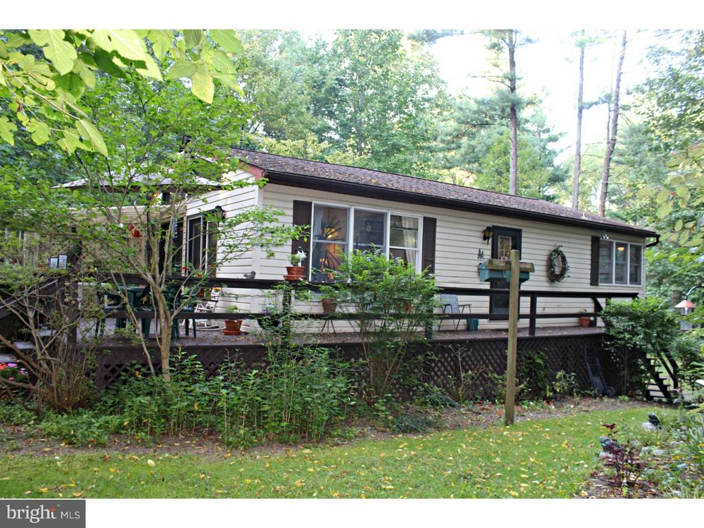 THIS COZY COTTAGE IN THE WOODS was built as a retreat and has served original owners well for 32 years! Enter into either the living room or the dining room through French doors from the deck or into the dining room from the front. The floor plan is totally open...a design way before it's time. The living room adds warmth from a propane fired fireplace, and it is open to the dining-room. Both rooms have wonderful views of the wooded setting. The kitchen is a continuation of the open concept with new self-cleaning gas range and refrigerator. Laundry appliances are conveniently housed behind folding doors off the dining area which also has multiple windows to enjoy the wooded setting. The Main bedroom is accessed from the kitchen with bi-fold doors to the bathroom which is also reachable from the living room. Attic storage is found from the bathroom, and the basement stairs are off the dining room. The large heated basement family room is waiting for your finishing touches, and leads to the heated 2-car garage. This well-hidden treasure also backs up to County Grounds surrounding the reservoir.