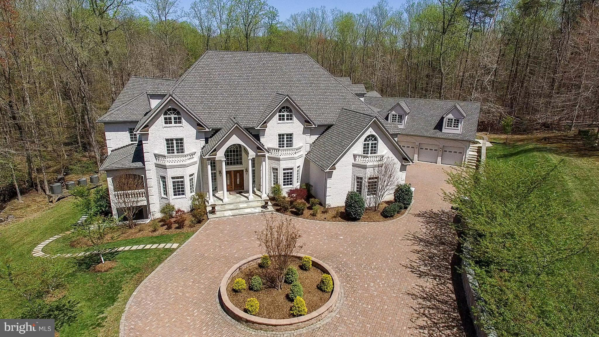 Masterpiece Estate nestled in the midst of 5 wooded acres in sought after Shadowalk. 4 finished levels with elevator. +10,000 SF of luxury living. Perfectly suited for both grand entertaining & comfortable family living. 2,000 SF indoor pool house. Gourmet chef's kitchen. Home theater. 6-car garage. 3 staircases. 5 master suites. 5 fireplaces. Access to extensive equestrian trails. Exquisite.