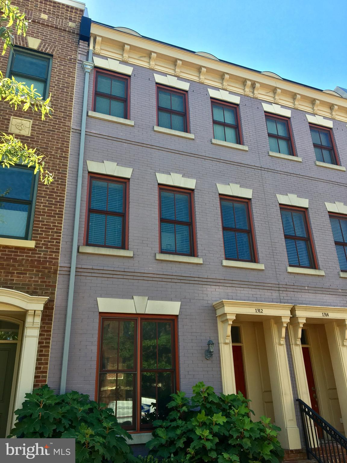 All brick 3 lvl TH in superb location - Bright light thruout - Granite kitchen - LR & DR gleaming wood floors & gas FPL - 3 en suite beds/baths - 3rd floor MBR suite w/luxury bath + balcony - bricked in patio - 2  garage spots - 2 blks to shops, grocery & restaurants - 4 blks to metro - 12 min to airport - Monthly fee covers most exterior, plantings, garage, fitness center, security. Lock & leave!