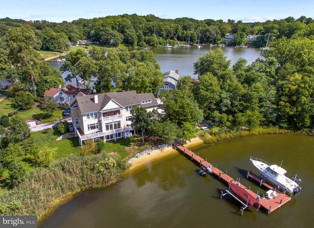 Located in the Parks at North Shore on the Magothy, this custom 2013 built waterfront home with 300+ feet of sandy beach frontage on two protected coves offers stunning water views from every room. Inside you will find an open floorplan perfect for grand entertaining and superb craftsmanship of the finest quality materials. Interior doors and mouldings were custom milled from solid Poplar. The robust front door with Emtek mortise lock was handcrafted of Ash. The spacious Kitchen features GE Monogram appliances, 6 burner gas range, double ovens plus microwave, two dishwashers, oversize Franke double bowl sink, reverse osmosis tap, large pantry, arrival center, and gorgeous White Princess quartzite counters. The main level Master Suite and Great Room with 10 foot ceilings include remote controlled Hunter Douglas shades and walkout to wraparound Trex deck. Dramatic Titan chandelier suspends above Dining Room with 26 foot ceilings and skylights. Secondary bedrooms all have wide louver plantation shutters and connected bathrooms with marble counters. The centrally located Great Room has 16 foot Pella sliding door with screen and Hunter Douglas remote controlled shade; coffered ceiling with Lightolier pinhole lites; Monessen Gas fireplace with anti reflective ceramic glass and remote controlled blower; and Dolby 7.1 surround sound with Polk Audio speakers and 18 inch Velodyne subwoofer. The distributed audio system with Marantz multi-zone amplifier and individual volume controls provides music to 5 zones inside and out. Upstairs you will find panoramic river views from the 14x20 foot covered porch with Big Ass Fan, hot/cold spigot, and radiant gas heater. An enclosed outdoor shower is located under the deck. Deep water pier offers 6 feet MLW and 3 slips including three remote controlled Magnum lifts; largest to 25,000 pounds. Energy efficient features include R26 closed cell spray foam and batt insulation; two zone 17 SEER Bryant Evolution HVAC systems with fresh air makeup and MERV 16 filtration; LED lighting with Lutron Masetro dimmers; tankless hot water heater with programmable smart recirculation; Grundfos constant pressure well pump; Hide-A-Hose central vacuum; and Pella Architect series aluminum clad windows with low-e, argon gas, and Sun Defense. Has extensive Cat5 & RG6 wiring, Verizon FIOS fiber optic, fire suppression system, Hunter Pro-C irrigation, and Lorex security camera system. Three garage bays with extra wide doors could accommodate up to 5 cars with optional lifts. The Glass House is your landmark when navigating back to Snapper Cove from The Point Crab House or nearby Dobbins Island. Contact listing agent for appointment. **Click Virtual Tour link for Floorplan Tour**