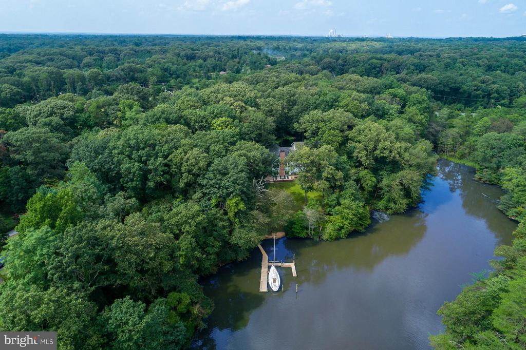 Tucked away on a protected cove, this Magothy River stunner feels like you're in your own private paradise! Meander down the 500 foot gravel driveway to another, very private, world. You are 600 feet from your nearest neighbors on one side, and Beechwood Park on the other. So much care and detail has been poured into this home. Enjoy water views from many rooms ~ including 3 of the 5 bedrooms, family room, great room, office loft and lady lair. Being this private doesn't mean the location isn't convenient. You are only 5 minutes to Lakeshore Plaza with a treasure trove of shopping, restaurants and daily conveniences like a Post Office, gas stations, grocery and banking. A mere two minutes to Rt 100 makes quick access to I-95, Baltimore and its attractions to the north or DC to the south. You won't have to deal with congested Mountain Road here! Your dock accommodates up to 5 boats, including deep water for your sailboat (ours can convey, if you'd like) The southern facing yard is perfect for gardening and sun-bathing. Need even more space? The basement has an in-law suite or rental apartment with full kitchen, living space, full bath, laundry and separate entrance to the backyard. The owners have thought of everything for this amazing home, we know you will appreciate the love and thoughtfulness throughout. Come visit us~you may never want to leave! Completed renovated in 2005 (including roof and mechanicals), Great Room addition in 2011 and in-law suite added this year. No flood insurance needed! County water (no well) and private septic system. Laundry on all 3 levels. Invisible fence to protect your pampered pets. Lovely landscaping includes seasonal plantings, vegetable garden and in-ground sprinkler system. Enjoy a crab feast in the picnic area - complete with picnic tables and benches! Nothing to do but move into this beauty.