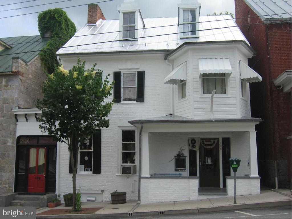 Two commercial spaces on main level and four apartment rentals in this downtown Shepherdstown main street building. Many original period features intact including original staircase, fireplace mantels. Large rear yard with four parking spaces off the rear alley. Covered front porch at 126 with knee walls for privacy.