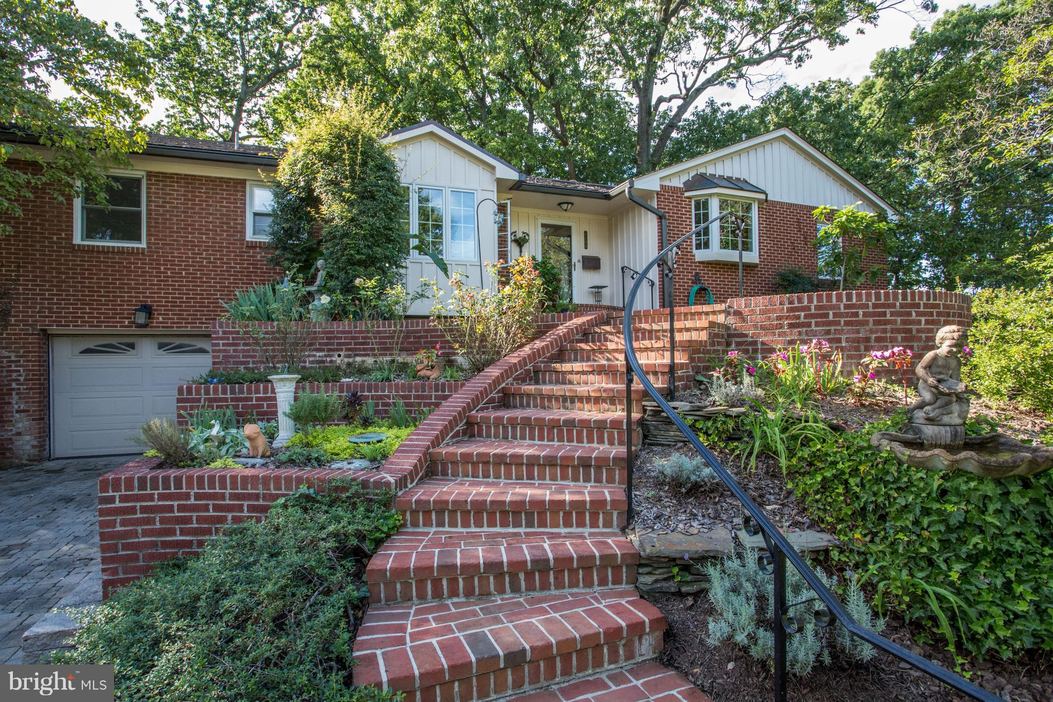 First Time for sale since it was built in 1956! Custom raised rambler set on a hill w/ spectacular landscaping and gorgeous garden patio w/ professionally installed lighting. Beautiful renovated eat-in chef's kitchen with large island, double ovens & table.  Lower level is fin w/ large recreation room, wood stove, kitchenette, in-law suite. perfect for entertain & loads of parking!