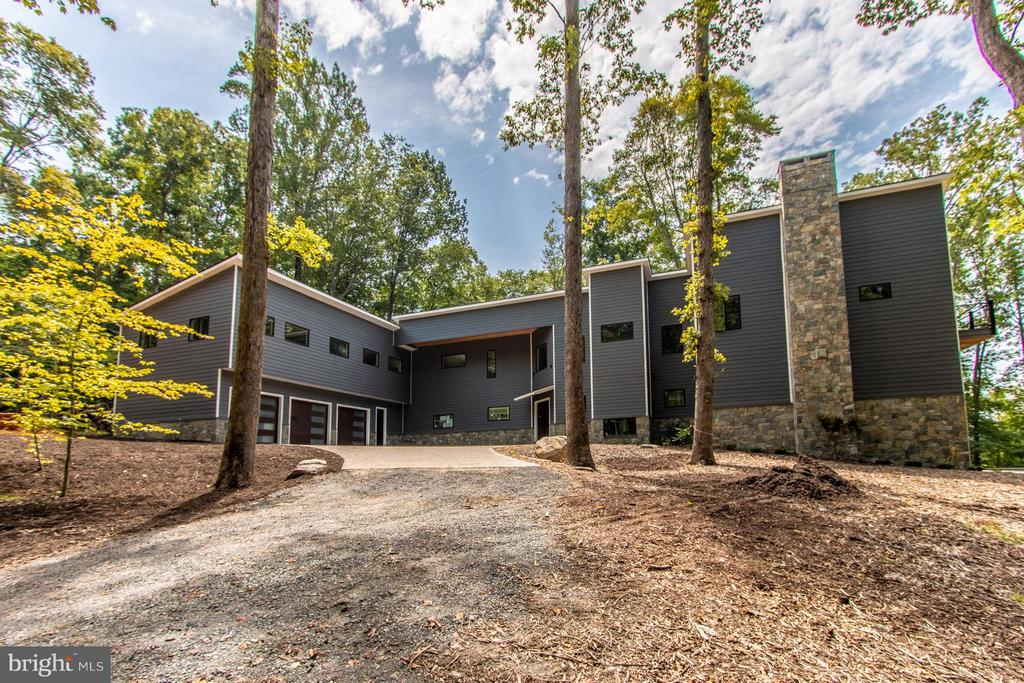 Spectacular one of a kind custom built  L shaped contemporary of hardy plank and stone with a 2 story exterior stone fireplace, paver driveway sitting on 5 private acres on 1000+ ft of the Occoquan River with views both north and south!  8000 sq ft 4/5 bedrooms, 5.55 baths, 3 levels facing west with scenic vistas from all the living space and 3 bedrooms! 3 car garage. Above the garage is a bedroom suite/inlaw suite/aupair suite w partial kitchen and full bath  as a wing to the gorgeous contermporary!  High ceiling ( 9.12.14 feet) and  open  floor plan!   Oversized double door solid wood entry to 2 story foyer. Elevator, deep coat closet, open offset metal staircase with wooden handrails to both the upper and lower level, plus second staircase! Huge full wall, floor to ceiling windows! 3 fireplaces- ll rec room, great room and master bedroom! Main level foyer entry, huge living room, separate dining room with  butlers pantry and deck access plus 2 half baths at either end. HUGE great room open to kitchen, island, customized cabinetry with quartz counter top luxury  SS appliances including subzero with front  window,  under the counter microwave, eurp styled double wall ovens, eurostyled gas downdraft  5 burner cook top, pocket handle dishwasher! Views from all room gorgeous but the great room overlooks the inground pool and the river! FIreplace and a wall of windows is breathtaking!Deck access from the great room with steps down to the pool! Upper level of main space has huge bedrooms, each with a balcony and a private ensuite bath! The master bedroom has a sitting area, fireplace, coffee bar, walk in closet and double closets, balony overlooking the river and the pool plus a glorious master bathroom with a separate soaking tub with scenic views, separate glass enclosed shower, private toliet and bidet toliet.  Gorgeous hardwood floors on two levels! Lower level features a stone fireplace, wall of windows with access to the  pool, plus an impressively organized utility room, wine cellar room, full bath! Heated floors, beautiful recessed and custom lighting ( the natural light is incredible).  Whole house generator, good for 7 days!  The pool will have an automatic cover, a self cleaning machine and has a water fountain feature with a level area for chairs plus deep water! SO much to LOVE. Please note the county descriped the quality as SUPERIOR!