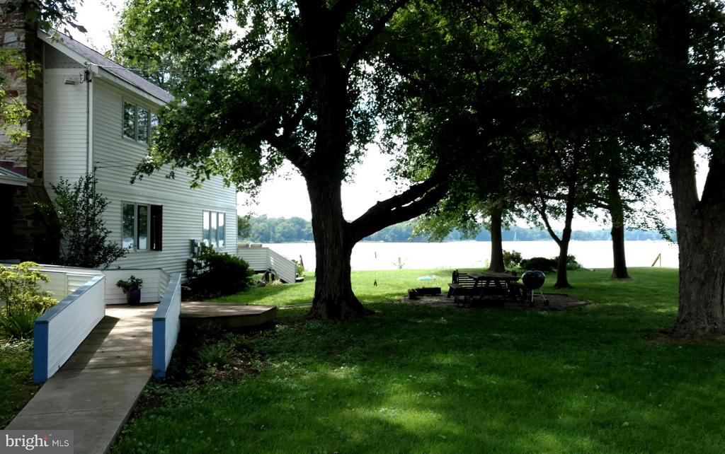 Renovated Waterfront home with an 85' pier, 104' of water frontage and 5' mean low water. This 2,400 sf home on nearly an acre was completely redone in 2000. With an open floor plan and views from every window, a 1st floor master bedroom and bath. Two additional bedrooms and bath on the upper level. Gourmet kitchen with tile counters and amazing storage and work space. Enjoy the spectacular water views all year long and spend time watching the wildlife. Your private pier on the Rhode River has electricity, a boat lift and lots of room for your boats, jet skis, kayaks and  other water toys. 5' mean low water and outdoor seating areas all around. Plus a beautiful salt water pool and a finished outbuilding that could be used for a bathhouse, guesthouse, workshop or studio. 3-car detached garage and ample additional parking.