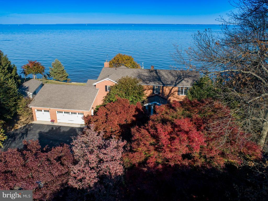 Extraordinary 5 bedroom 3 Full bath Brick Colonial located on 1.24 acres in coveted Windmill Point and just a stone's throw from Gibson Island. Featuring breathtaking panoramic views of the Chesapeake Bay visible from floor-to-ceiling windows in main living areas & bedrooms . 3 Finished levels provide over 3800 sq ft of living space with a main level perfect for entertaining. Custom renovated kitchen with top of the line upgrades including cherry cabinets, ceramic tile backsplash, Wolf 4 burner gas cooktop/double wall oven & built-in sub zero fridge/freezer. Breakfast area overlooks lush, private yard & family room off kitchen highlights large stone fireplace and access to screened in porch. Upstairs offers 5 generous bedrooms including a stately Master Suite with dressing area and walk-in closet. Master Bath is like a spa right at home with radiant heated marble floors, custom vanity and marble rain-forest shower. Private 110 ft. pier with 2 boat slips, electricity and 1 boat lift. This stunning home is a MUST SEE!