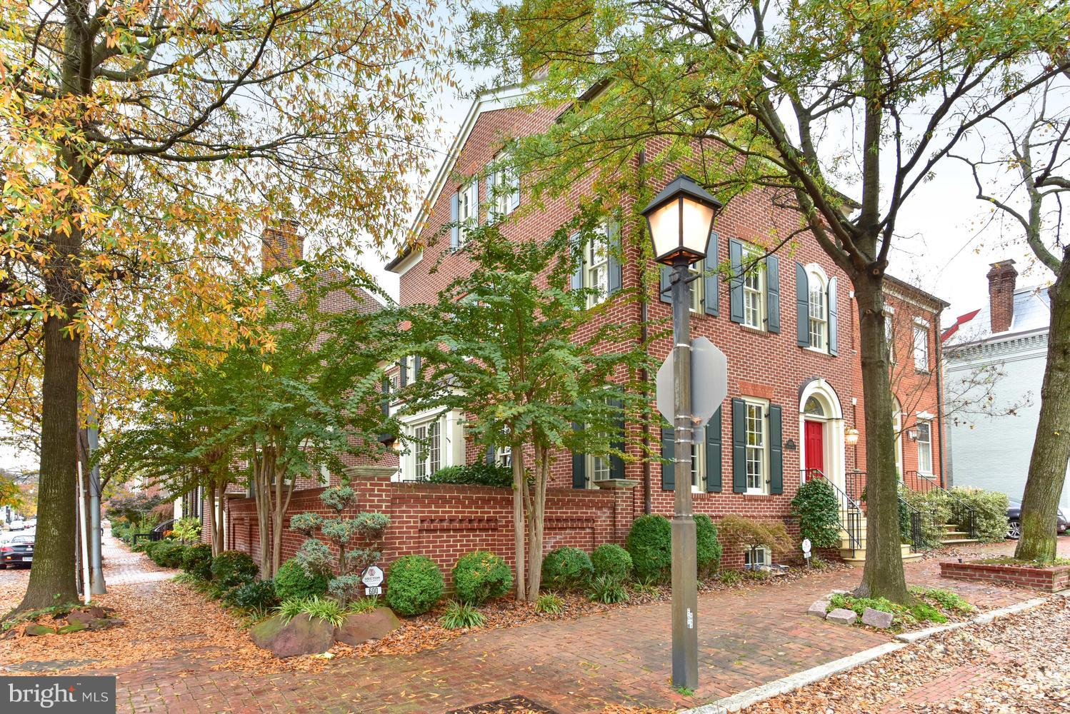 The stately brick Alexandrian at 600 Princess Street is sited proudly off Old Town~s historic cobblestone street.  Ascend a gracefully curving front staircase with wrought iron handrail to enter through a double front door, illuminated above by an arched transom window. The foyer's soaring ceiling draws the eye upward to the glossy hardwood staircase, as well as offers gracious entry to a well-appointed sitting room with a marble surround gas fireplace, sunny window exposure and handsome columns framing the room. Straight ahead, take a direct path to the main floor half bath or open the door discreetly closeting the elevator.  From the sitting room, enter the dining room surrounded by elegant wainscoting. It's tucked neatly between the kitchen -- accessible by French doors -- and the two-level brick courtyard. The dining room looks into the top level, with a pergola that beckons for blooming flowers and trailing vines. On the second level, a romantic fountain promises a soothing backdrop for entertaining or a quiet morning spent with coffee and newspaper. The kitchen is outfitted with every device and storage system a contemporary cook needs. While the gleaming copper range hood is the show-stopping focus of the room, utilitarian tools like a trash compactor, custom cabinets and drawers, wood-paneled Sub-Zero fridge and deep sink will serve daily needs from easy meal prep to sufficient stashing of fresh and perishable pantry goods. Access the garage through the kitchen, or step down a flight of stairs into the finished basement.  A bank of windows ensures this subterranean space never goes dark, and the gas fireplace ensconced within a rustic stone wall ensures extra glow on the darkest winter days. This space is idea for casual entertaining, with its fully equipped wet bar. It could also serve a family~s needs for guest quarters (a full bath is just around the corner from the bar) or even a quiet office or fitness space. On the second floor, a master suite haven awaits behind two sets of French doors. One set opens into a well-sized sitting room with a wall of plantation shutter-dressed windows that stands opposite a wall with built-in bookcases. Between the two walls stands the home~s third fireplace, making this space a perfect reading room, office, sanctuary -- or even nursery, given the proximity to the master bedroom. Storage and luxury abound in this carefully planned space. Two custom shelving areas offer four seasons~ closet storage, and a sunken bathroom is a spa-like retreat with its deep whirlpool tub, glass-enclosed shower, expansive double vanity countertop, and private water closet complete with bidet. Vertical linen and toiletries storage completes the space -- and a pastoral fresco above the tub elevates it. On the top floor of the house, two additional bedrooms and a full bath accommodate the household's growing needs. Windows dressed with plantation shutters filter sunlight, and generous closet space (as well as attic access) keep clothes, luggage and other items organized. The street-facing room features built-in shelf, cabinet and desk space to streamline work and storage space. With Old Town's bustling dining and shopping scene mere blocks away, 600 Princess is well-positioned for evenings out. And mornings out are a snap, too, with cafes in quick walking distance and easy access to major roads leading into Washington.  Access the Metro system by Old Town's cheerful trolley or bus system.  Enjoy a view of the Potomac by strolling a short distance to the waterfront, where the Mt. Vernon trail joins downtown sidewalks and offers the perfect route for a run or to walk the family dog. **WALK THROUGH THE HOME WITH OUR VIRTUAL TOUR IN VIDEO SECTION**