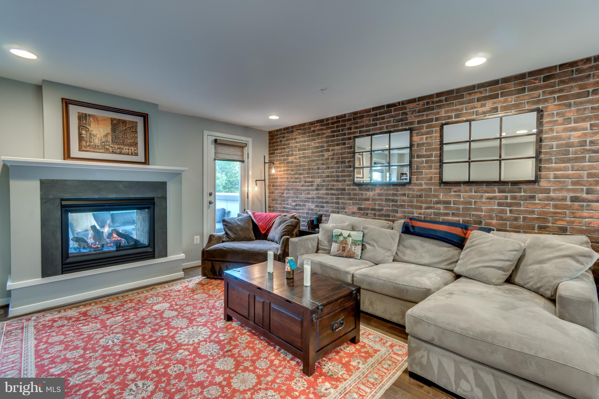 """Perfection = Quintessential Old Town Alexandria Charm with newer construction - only 4 years old!  Location that can't be beat!  Only 1/2 mile to Braddock Metro, 1 mile to National Landing, 3 miles to Amazon HQ and 4 miles to Pentagon!  Surrounded by shops, restaurants, grocery, playgrounds, dog parks, and trails - you won't even need the attached 2 car garage!  Over $120k in upgrades including: in-wall / in-ceiling speakers in 3 rooms, dark hardwoods in common areas, premium carpet in bedrooms, gourmet white kitchen with solid maple soft-close 42"""" cabinets and granite counters / spacious island,  natural gas grill on deck off kitchen that conveys,  luxury marble master shower with dual shower heads and body jets, custom ELFA closet organizers,  dual-zone smart home HVAC systems (ecobee), plantation shutters and blinds on all windows & patio doors, bedroom-level full size HE laundry,  en-suite full bathrooms for both 3rd level bedrooms,  Kohler faucets,  Benjamin Moore paint palette & crown molding throughout,  Smart Lighting - vacation mode & exterior auto-on at dusk.  Entertain in style:  warehouse vibe loft with exposed brick wall and indoor / outdoor natural gas fireplace that passes through to your rooftop deck with views of National Harbor, Old Town and even the Washington Monument!  Need an extra bedroom?  No problem!  Add 1 wall in the loft to create a 4th bedroom with en-suite full bathroom.Ground level office/bedroom."""