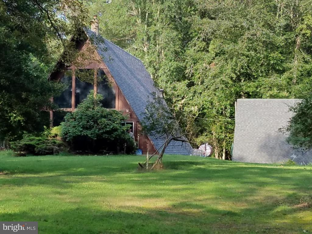 This unique one-of-a-kind A-frame with 2 bedrooms and 1 1/2 baths is nestled among the woods on 12.40 acres.  Entering down a long paved driveway,it affords you complete privacy.  As you enter the A-frame, the entire wall is made up of glass.  As you step inside the great room there is a sunken fire pit that you can utilize to heat your entire home.  An attached potbelly stove makes for more efficient heating.  The Great Room has a cathedral ceiling and is comprised of a living and dining area, kitchen and wet bar.  The wet bar's base is made up of real stones. There is a large bedroom on the first floor with an en suite bathroom and an attached sun-room with three skylights. Climbing the spiral staircase leads you to the loft with a sitting area overlooking the downstairs and the lawn outside. The room behind has the bedroom and the half bath. From the loft you can ascend another flight of steps into the Attic which is used for storage but could possible be used as a third bedroom. The roof was replace 2 years ago and the house was stained in 2017. There is an Oil Forced Hot Air Furnace and Central Air Conditioning.  All the appliances are included.  Outside, there are two workshops and one garage, a pond as well as an in ground swimming pool with its own separate water supply.  Don't miss this opportunity to own your own piece of nature.  Property being sold as is.