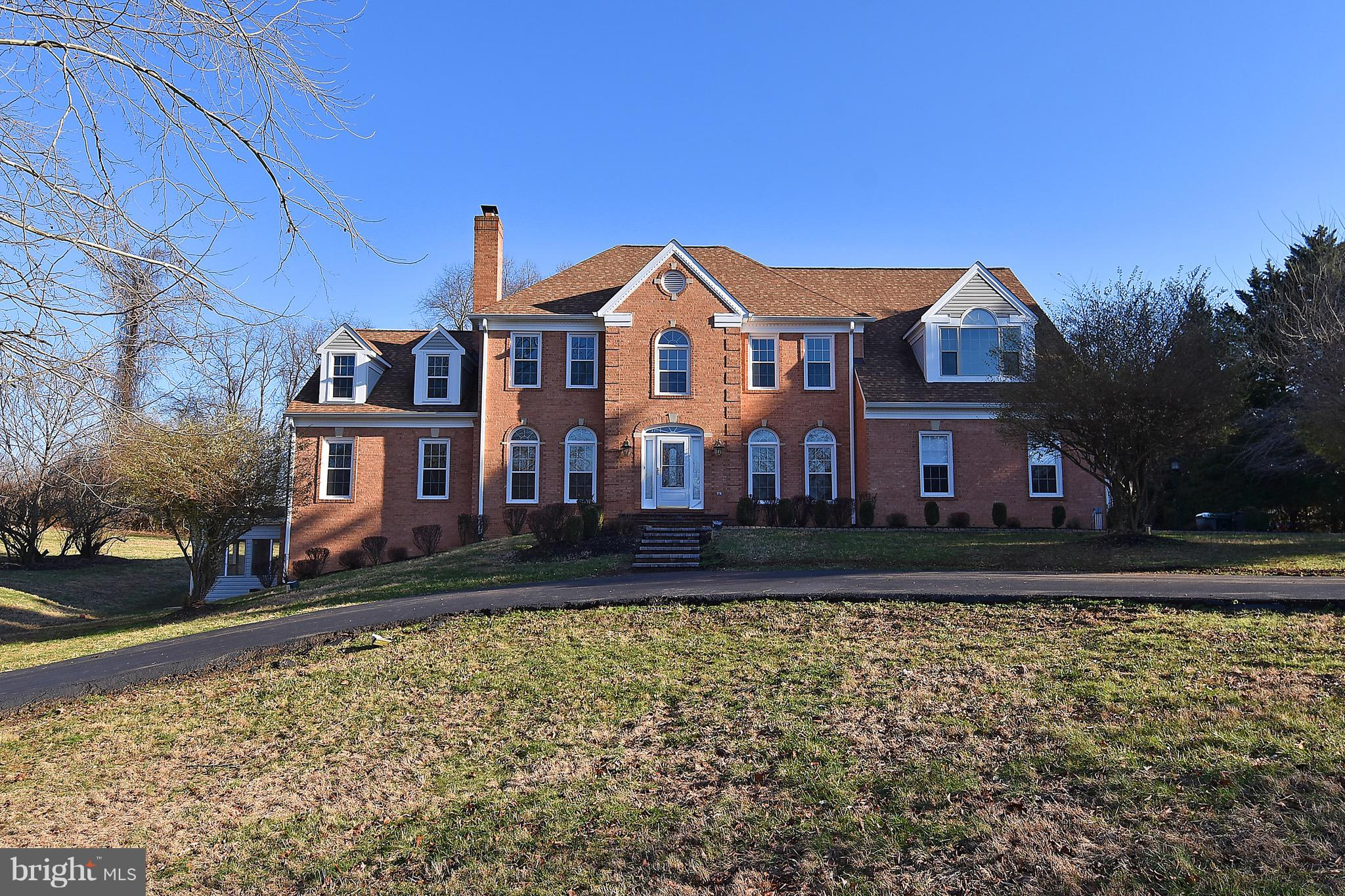 Spectacular Double Wing Brick front Georgian Colonial in the wonderful, classy, Windsor Gate community. Over 6 gorgeous acres!   A circular driveway welcomes you to this suburban oasis which offers 5 bedrooms, 4 full baths and 2 half baths. The high ceilings, light & bright interior and embassy sized rooms  are perfect for entertaining on a large or small scale. The main level offers a 30 foot high ceiling great room with vaulted ceilings,  plus 1st floor family room and library, with 3 fireplaces. . The large gourmet kitchen is sure to delight the most particular cook.. Upstairs offers a large master suite with sitting room, large walk in closet and stunning master bath with Luxury whirlpool tub and separate shower...  PlusThree  more large bedrooms and 2 full baths  and a large laundry  area. The lower level is completely finished with a bedroom, full bath, game room, office and florida room....Welcome home!!