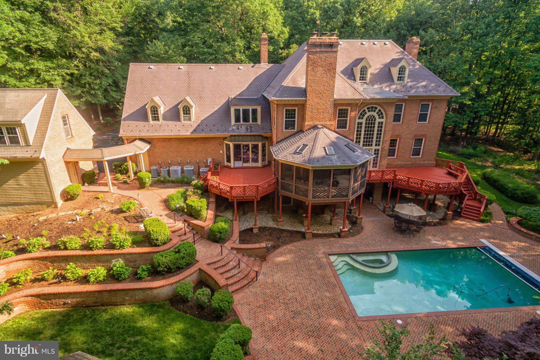 A light-filled Williamsburg styled Colonial Revival mansion on a quiet country lane in Clifton, Virginia, has everything you need for privacy and comfort not far from the city. And the systems running behind the scenes add even more to this home~s unique appeal. Starting with the exterior, 13101 Loth Lorian Drive, offered at 1.95 million, is a picture-perfect, large three-story, brick house with another level below-grade, and has about 12,000 square feet of living space. A double staircase leads to a welcoming front door that is encompassed by a two-story Palladian window, which floods the first-floor and central staircase inside with sunlight. The entry hall and great room of the home are illuminated by two grand chandeliers, plus a fixture in the adjacent dining room sparkles with a multitude of large Swarovski crystals. The home has seven bedrooms, seven bathrooms and two half-baths. A second, two-story Palladian window opposite the one on the fa~ade allows for panoramic views of the pool and surrounding woodlands.  (Some have noticed a resemblance between the home and Long & Foster~s Chantilly, Virginia, headquarters, which also is designed in the early American style.)The current owner, added a three-car garage with an au-pair suite, blending it seamlessly with the existing architecture. Other enhancements can~t be seen but perhaps are detected in the air. He also purchased a system that brings in outdoor air, scrubs it through a filtration system, and exchanges it with stale indoor air to keep the dust down, making the air so clean that it doesn~t give your upper respiratory tract a beating.  Being an ENT Surgeon, he does know what he was doing to make the air as clean and fresh as an operating room.  Other improvements included four steam humidifiers, a whole-house vacuum system, two tankless gas water heaters, and extra attic insulation. The home also has two enterprise-level wifi hotspots and a firewall, to aid with conducting business securely over the internet from home.  Additionally, they installed a whole-house generator that can power the entire property including the pool, along with a battery backup that can run the house for 24 hours if the main system fails.Situated 28 miles west of Washington, D.C., on five acres, the property has ample outdoor entertaining space. Two large decks and a screened gazebo overlook the pool, which is surrounded by terraced landscaping and a brick patio. An Otis elevator to all 4 levels, makes it easy to transport refreshments and accoutrements for entertaining from the kitchen to the lower-level pool and patio.